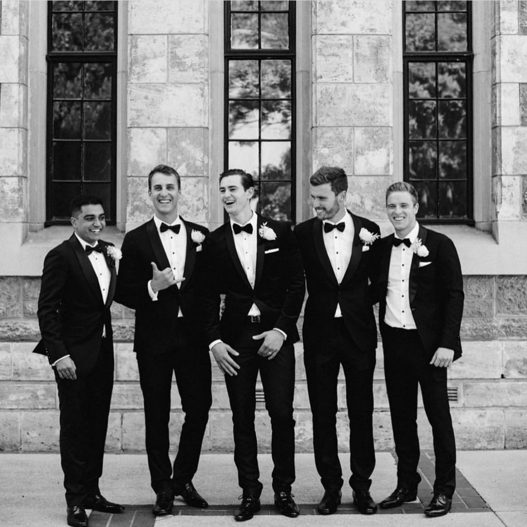 Groomsmen and Groom wearing tuxedo black tie suit
