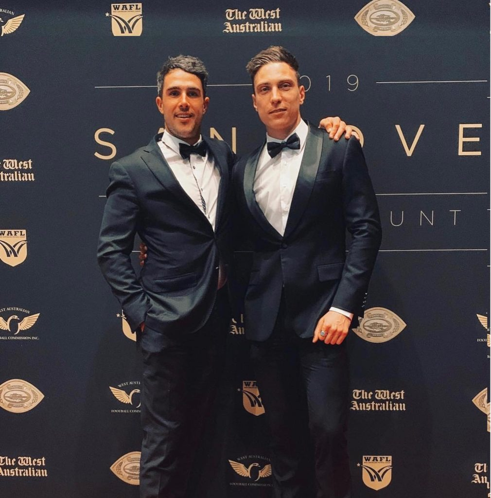 two men wear identical black tie suits with bow tie