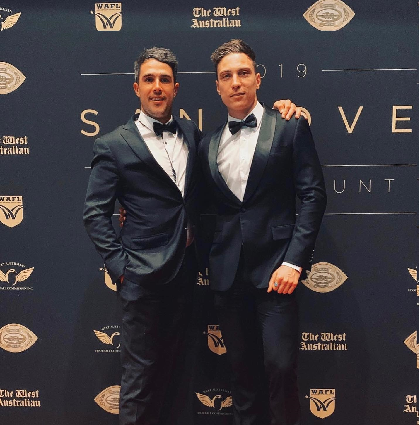 men-wearing-matching-black-tie-suits-with-bow-tie